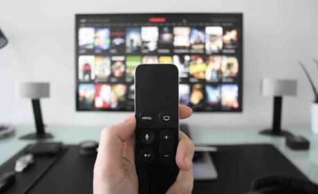Person holding a remote to TV showing Netflix