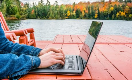 Person typing on a laptop outside by the lake