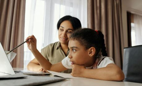 Mother & Daughter sitting at the table on a laptop