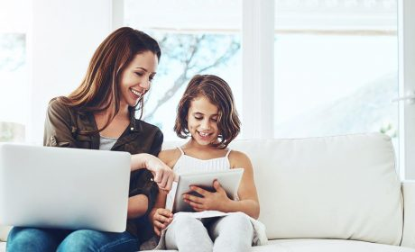 Mother on her laptop & daughter on a table both sitting on the sofa