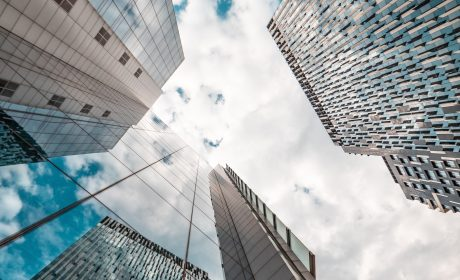 A photo looking up at the sky between three skyscrapers.