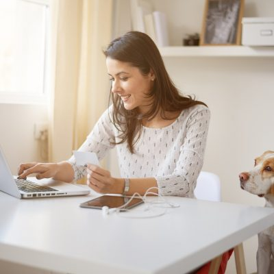 Woman sitting down in front of a laptop with a dog by her side