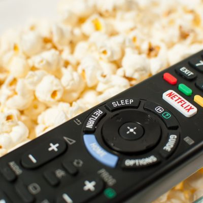 TV Remote sitting on top of a bowl of popcorn