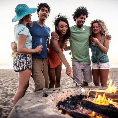Group of friends at the beach in front of a fire pit melting a marshmallow