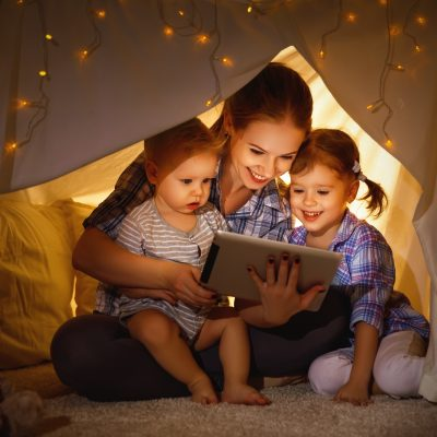 Mother with her to children using a tablet whilst sitting under a blanket fort