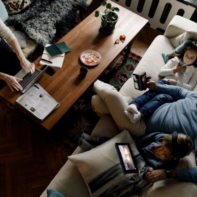Family sitting down in the living room using their devices