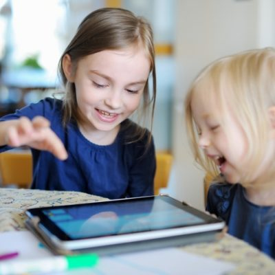Two girls playing on a tablet at the table