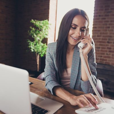Woman using a home phone sitting in front of laptop