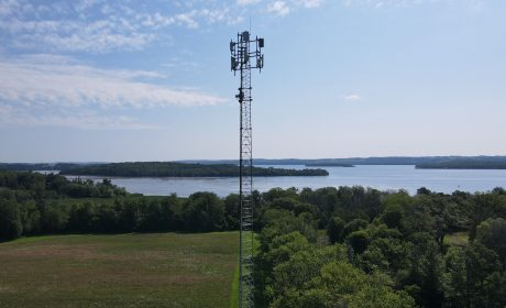 A cell tower overlooking a landscape of trees and a body of water