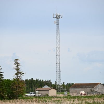 A photo of a cell tower located on a rural property.